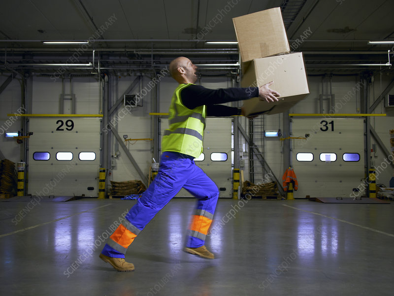 Worker balancing boxes in warehouse