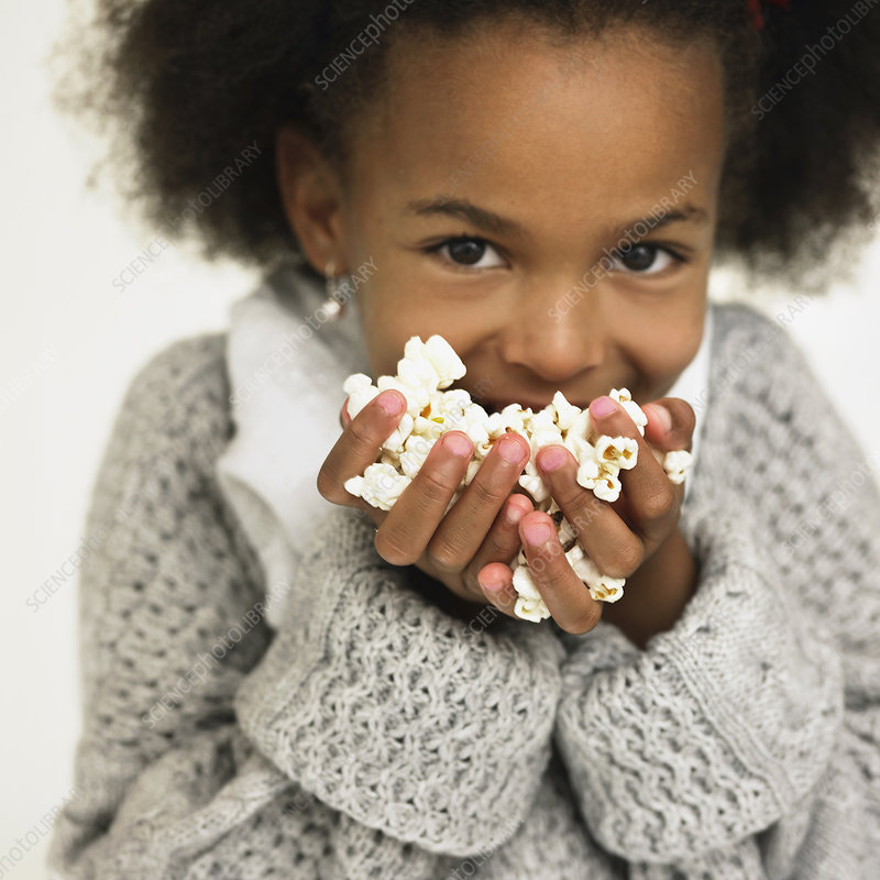 Girl eating handful of popcorn