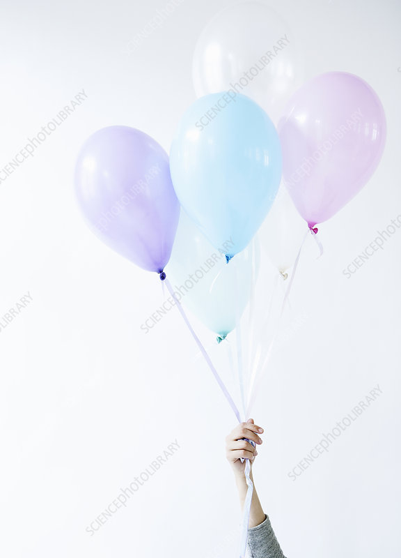 Hand holding bunch of balloons