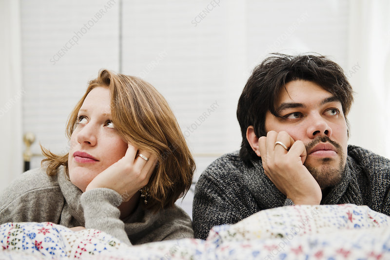 Couple resting chins in hands on bed