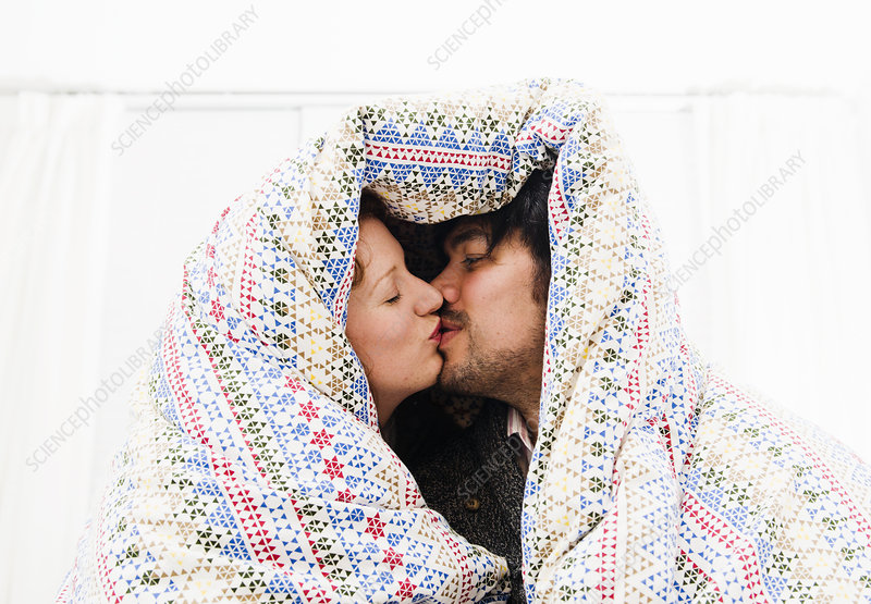 Couple kissing under duvet blanket