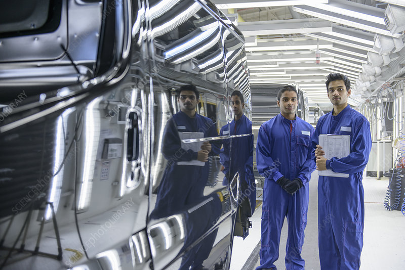 Workers standing in car factory