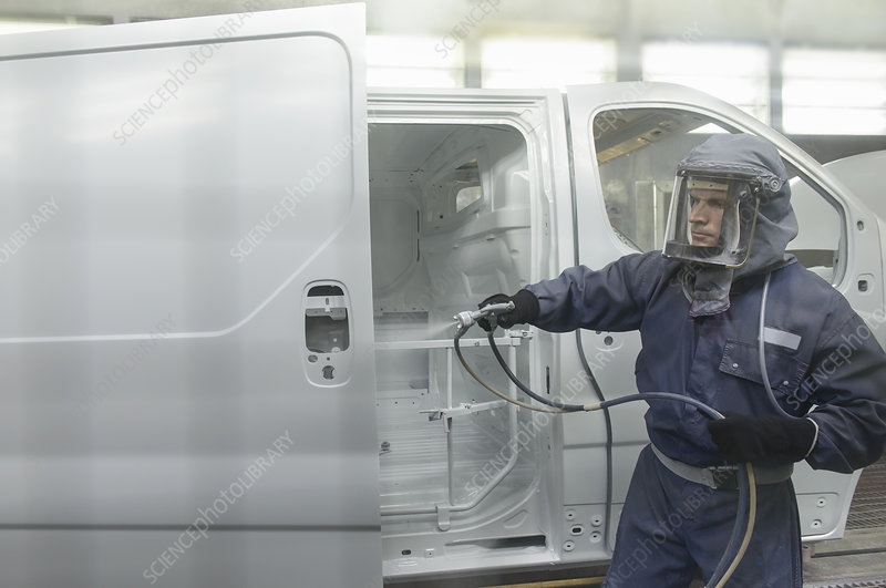 Worker spray painting in car factory