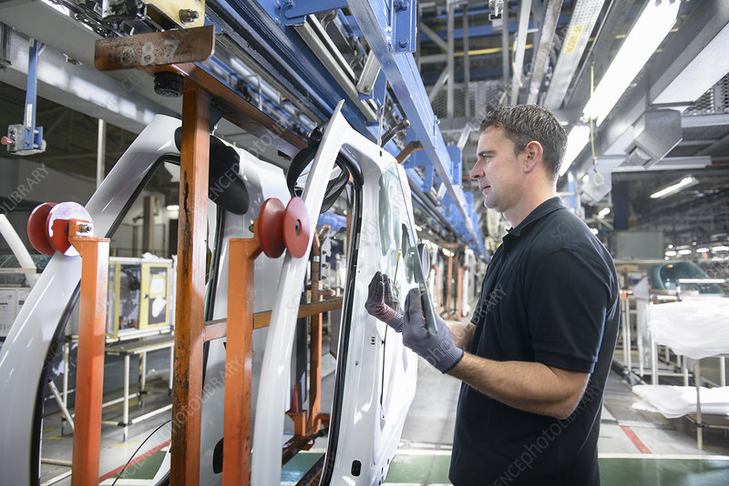 Worker fitting parts in car factory
