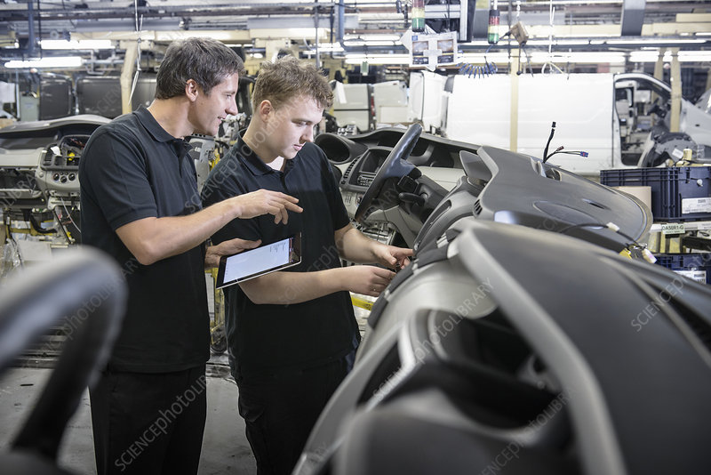 Apprentices working in car factory
