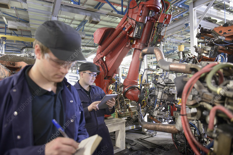Apprentices with robots in car factory