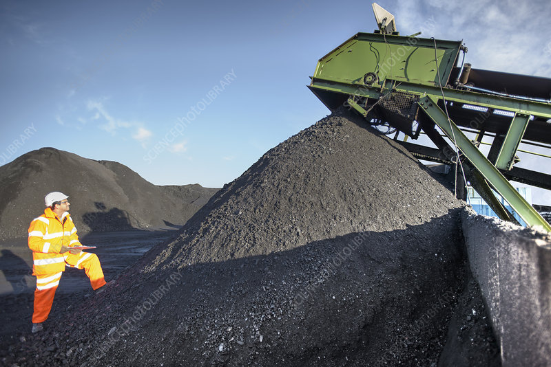 Worker examining pile of coal at mine