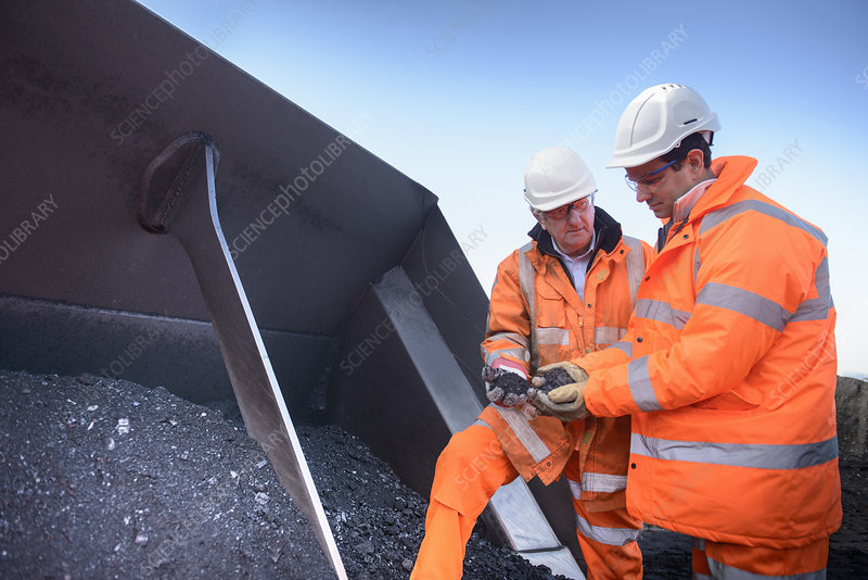 Workers inspecting coal at surface mine