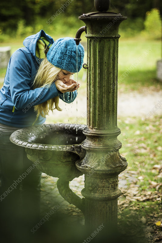Woman drinking from water fountain