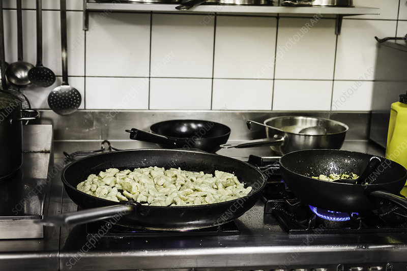 Pans of food cooking on stove