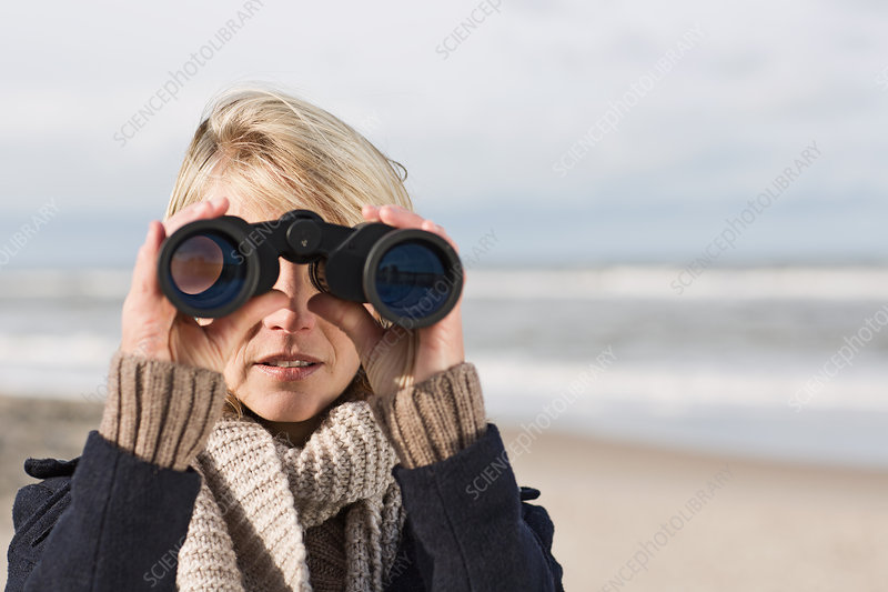Woman using binoculars on beach
