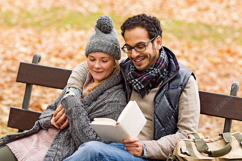 Couple reading together on park bench