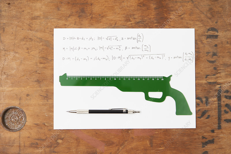 Gun shaped ruler and pen on paper