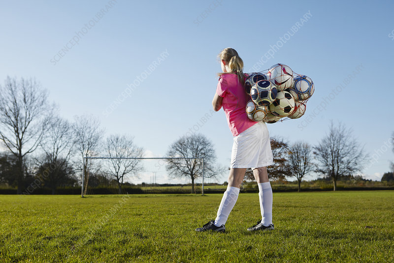 Football player carrying balls in field