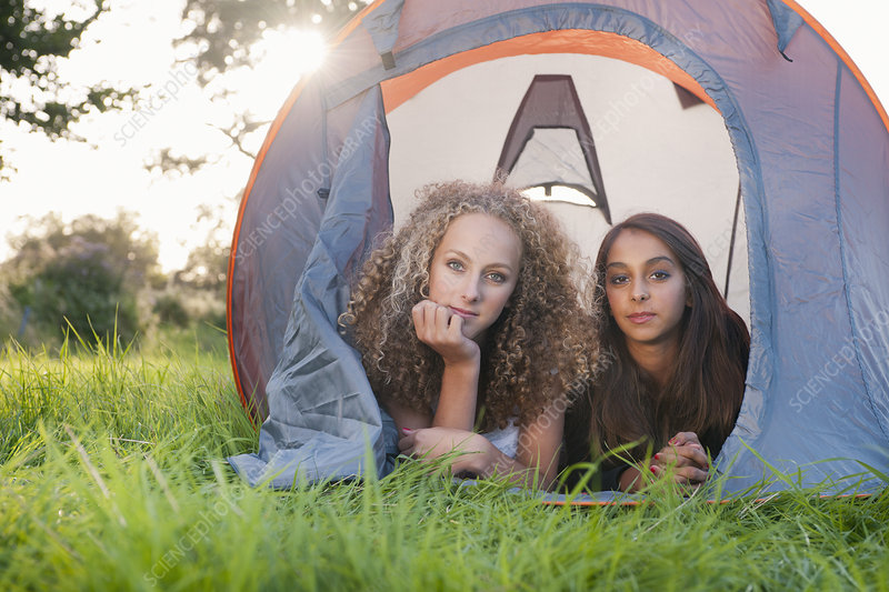 Teenage girls laying in tent at campsite