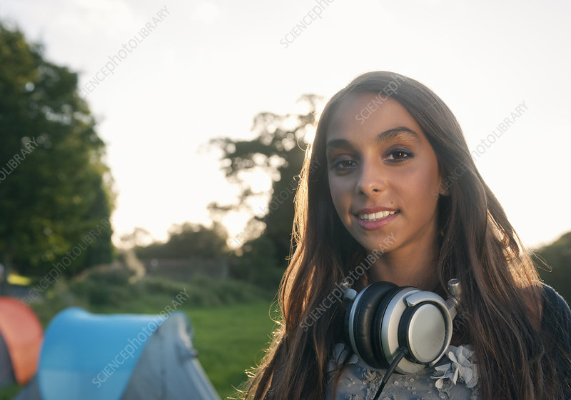 Teenage girl wearing headphones outdoors