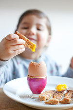 Girl dipping toast into egg at breakfast