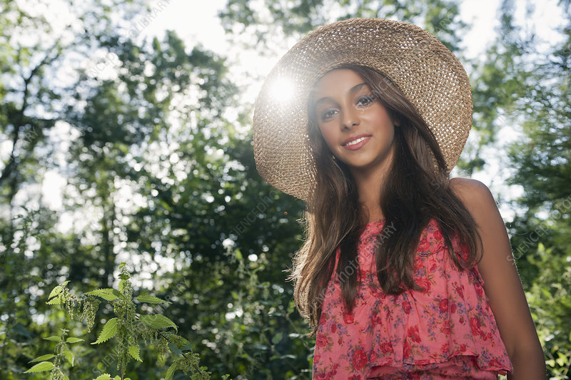 Teenage girl wearing straw hat outdoors