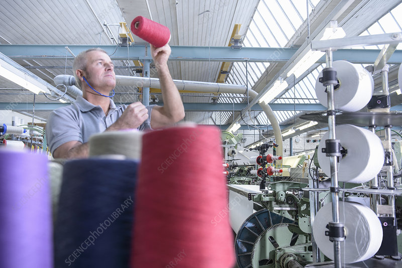 Worker examining thread in textile mill