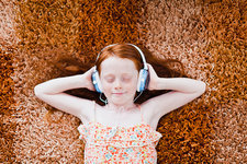 Girl listening to headphones on carpet