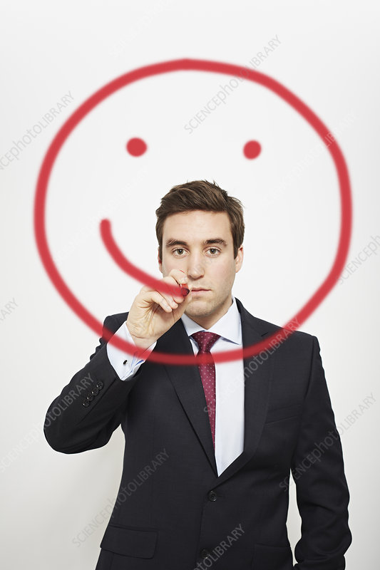 Businessman drawing smiley face in air