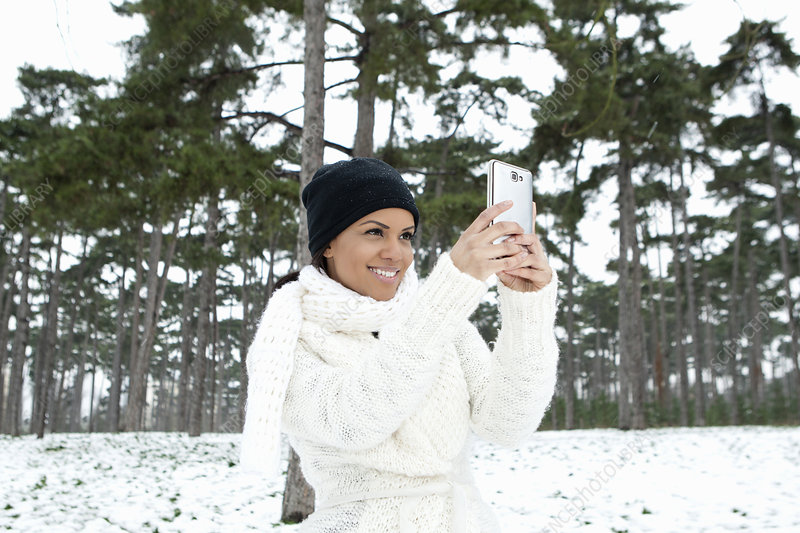 Woman taking picture in snowy forest