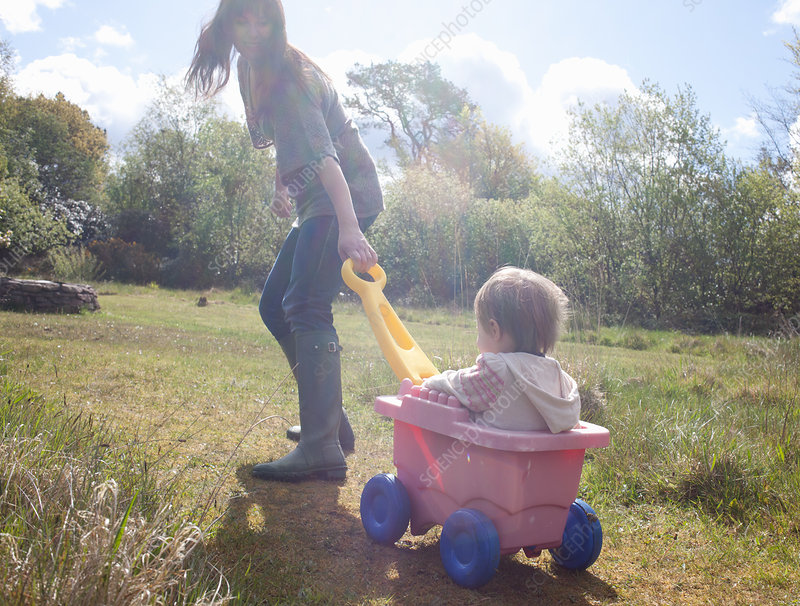Mother pulling toddler girl in wagon