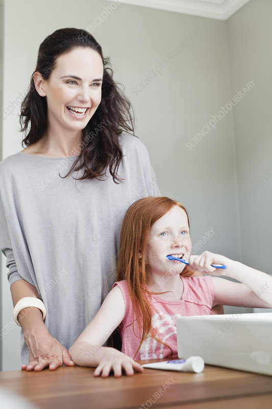 Mother watching daughter brush teeth