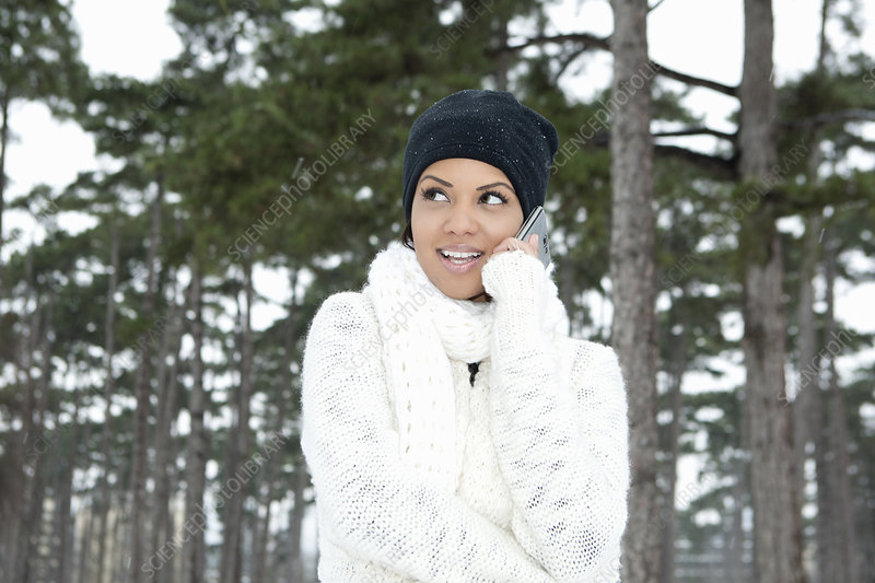 Woman on cell phone in snowy forest