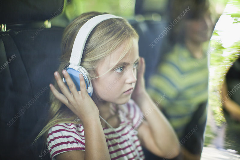 Girl listening to headphones in car