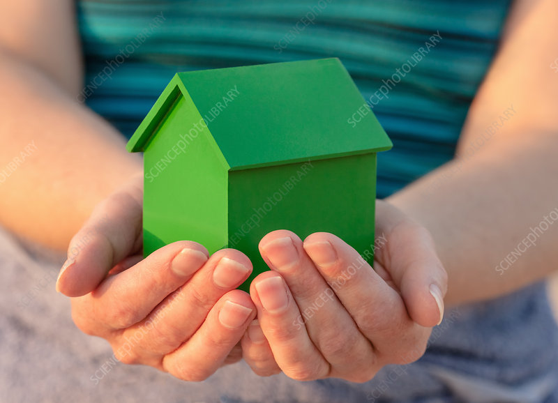 Hands holding model house outdoors