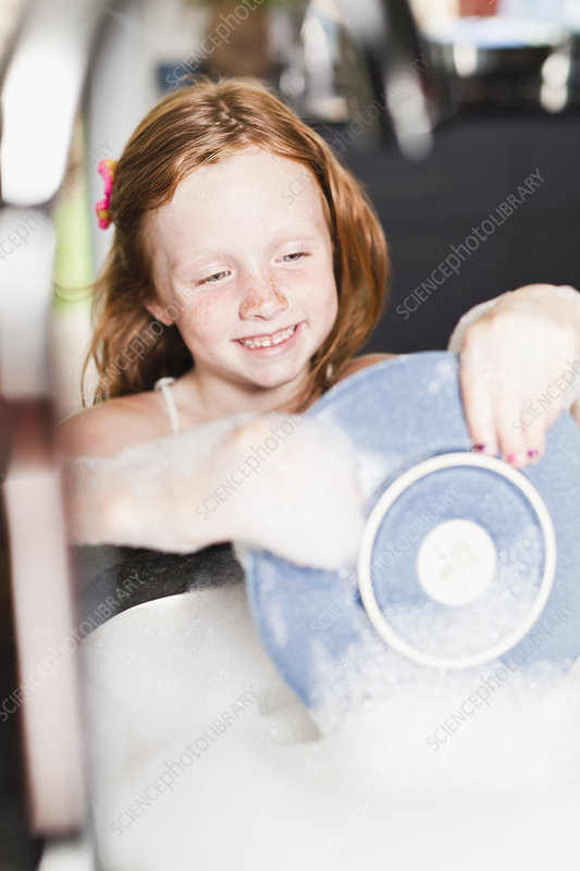 Smiling girl washing plate in sink