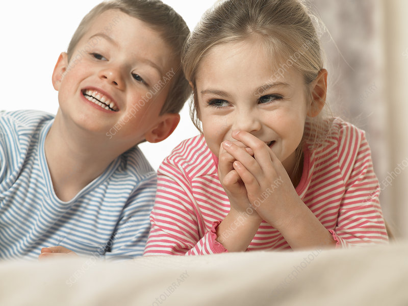 Children laughing together on bed