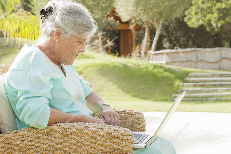 Older woman using laptop outdoors