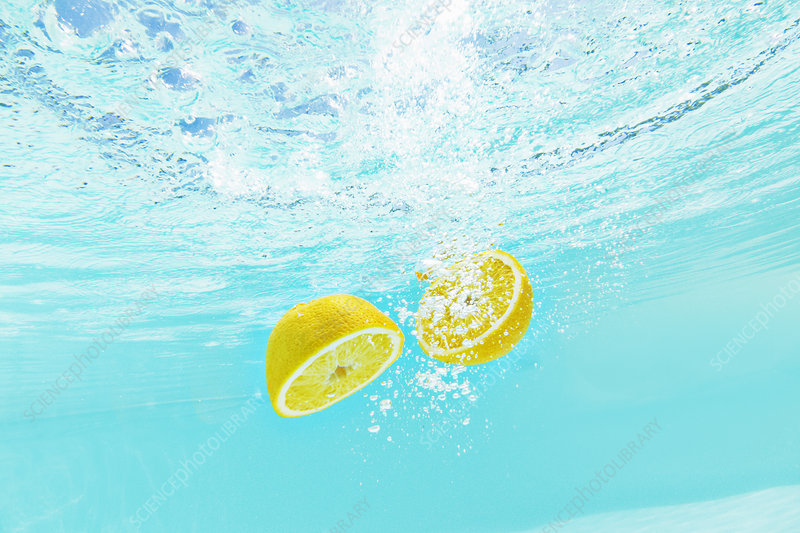Sliced lemon splashing into water