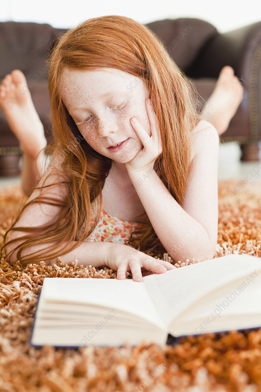 Girl reading on living room floor