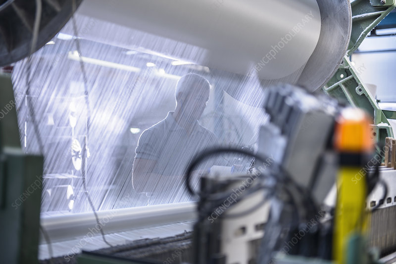 Worker using loom in textile mill