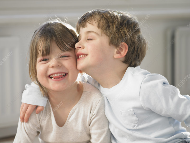Smiling children hugging indoors