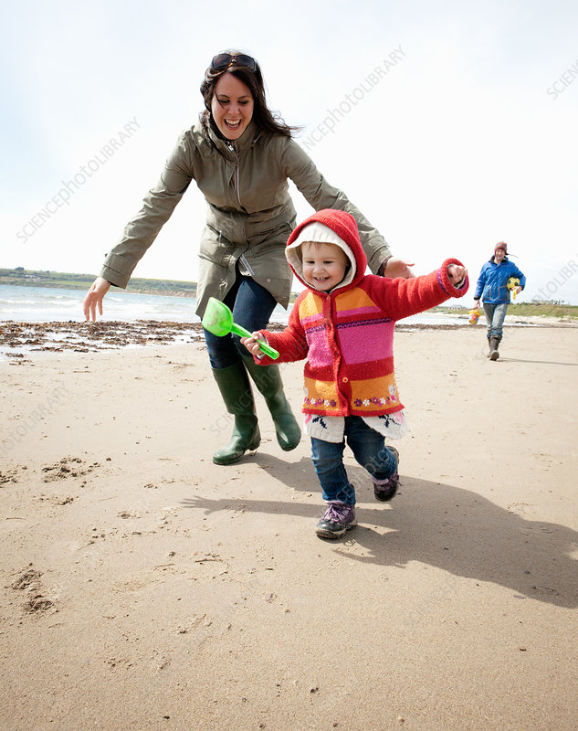 Mother chasing daughter on beach