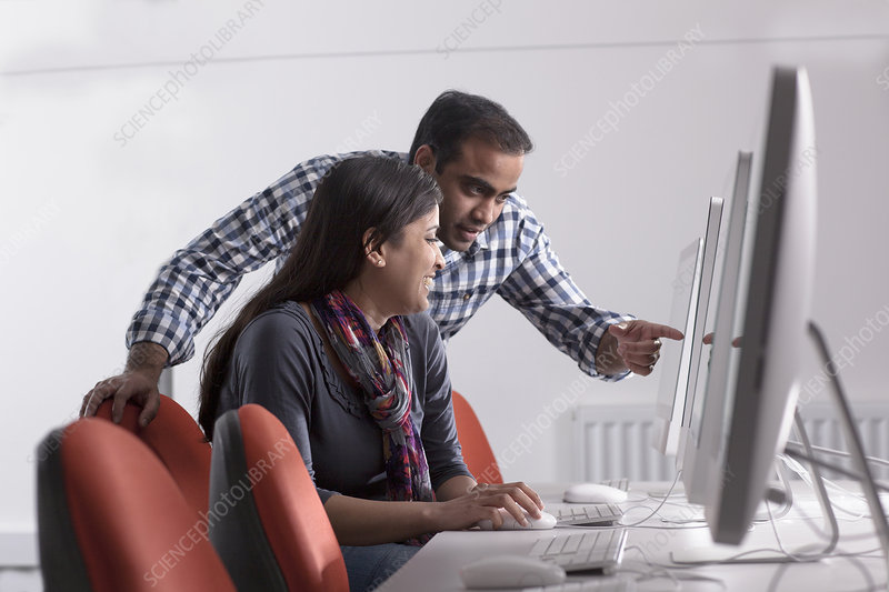 Couple using computer at desk