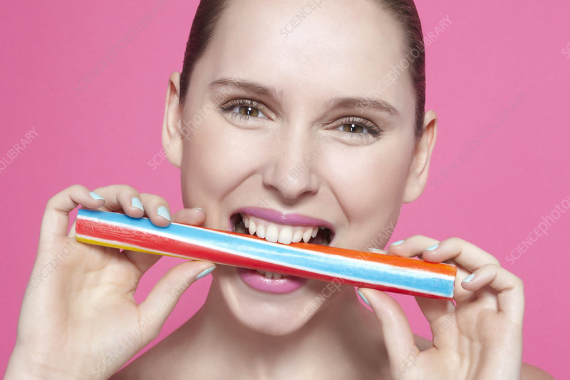 Smiling woman biting candy