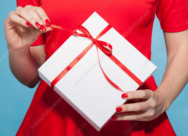 Woman opening white gift box with red bow