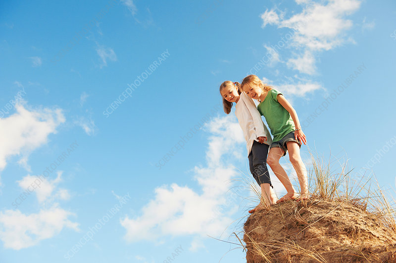 Two girls standing on edge of sand dune