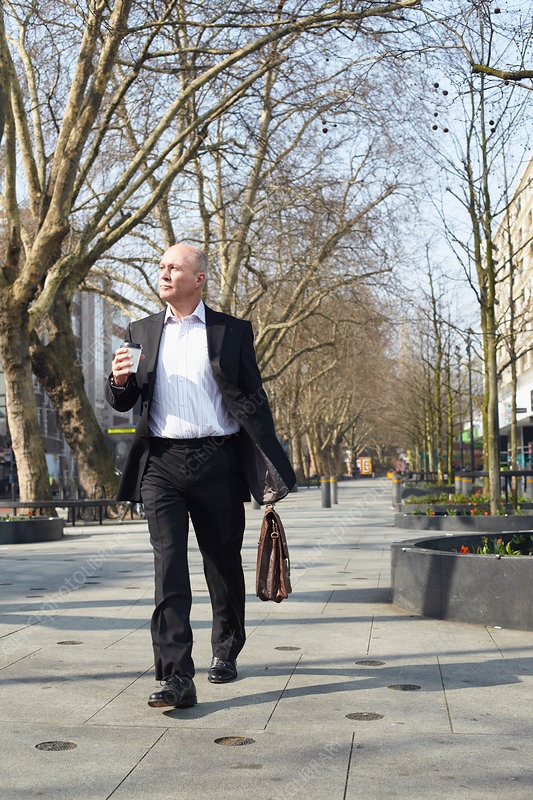 Businessman walking with coffee
