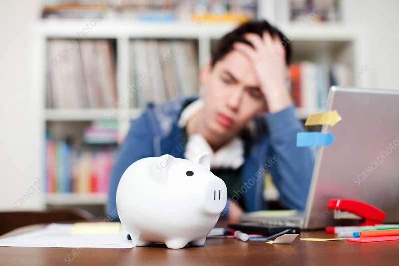 Piggy bank with worried young man