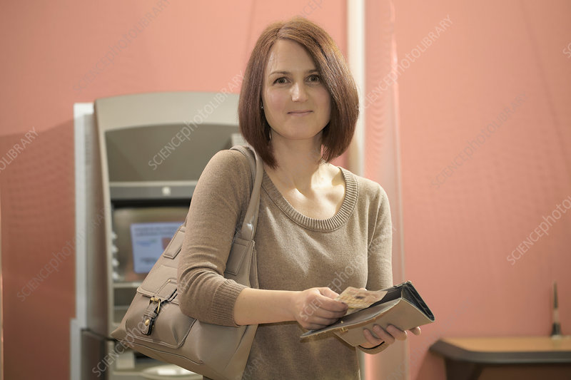 Woman putting banknotes into purse
