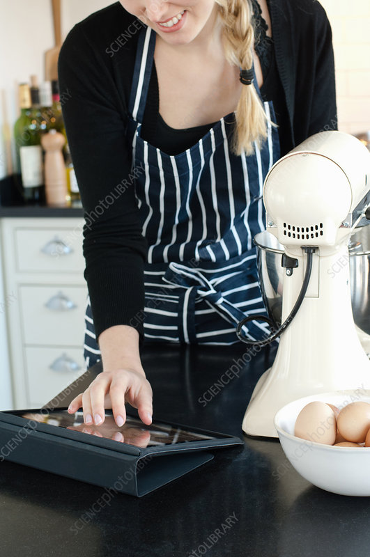 Woman using tablet to check recipe