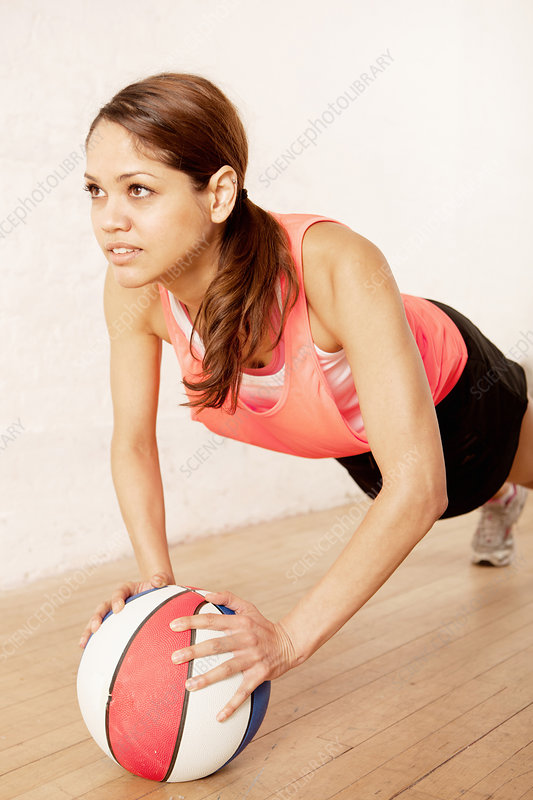 Young woman doing press ups on basketball