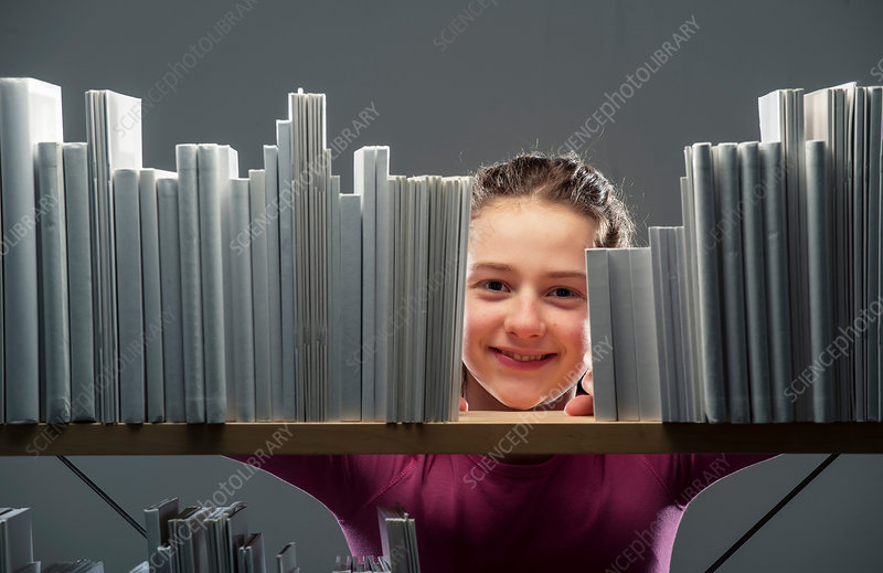 Girl peeking between books on bookshelf