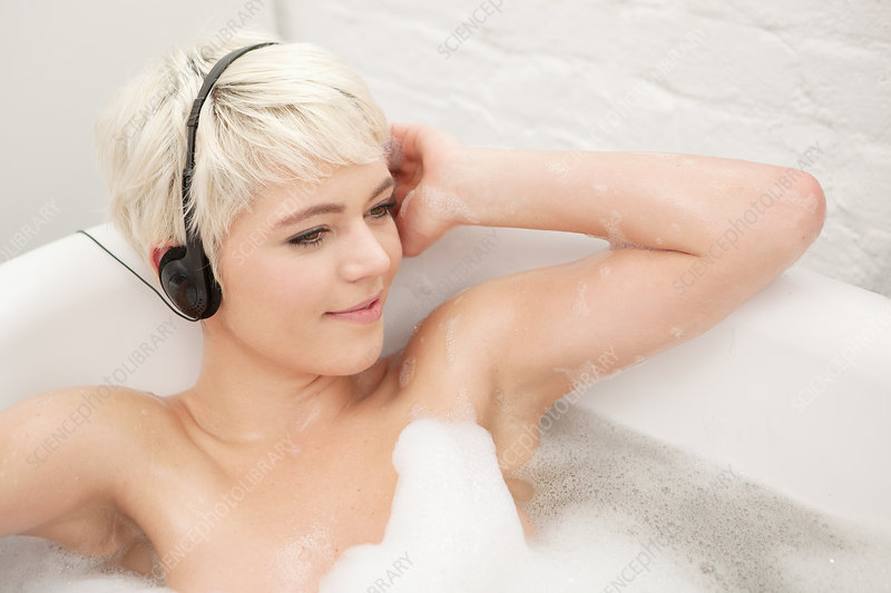 Woman in bubble bath wearing earphones